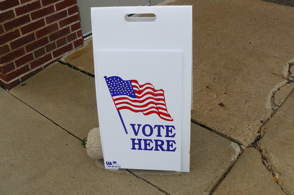 Ein Schild mit der US-amerikanischen Flagge und der Aufforderung: Vote here (Wählen Sie hier).
