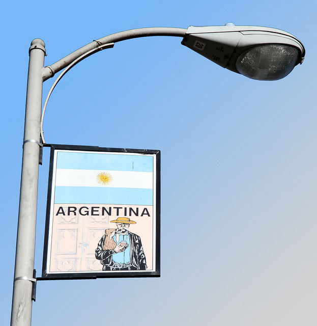 A sign with the national flag of Argentine and the drawing of an elderly man with a straw hat and a typical mate tee calabash in his hands hangs under a street light.