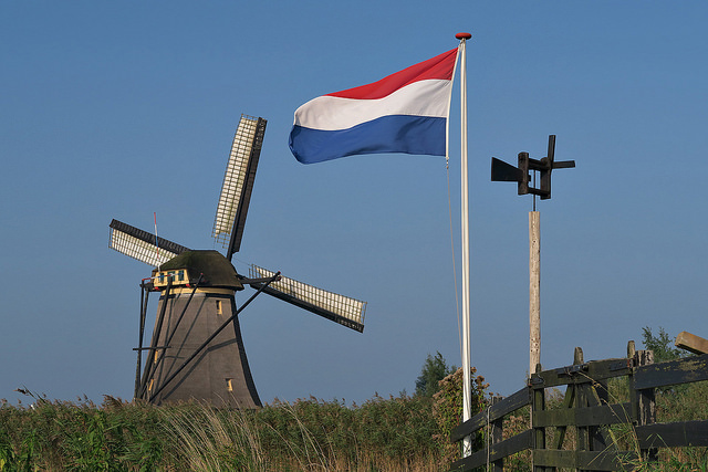 A Dutch flag in front of a windmill, one of the emblems of the Netherlands.