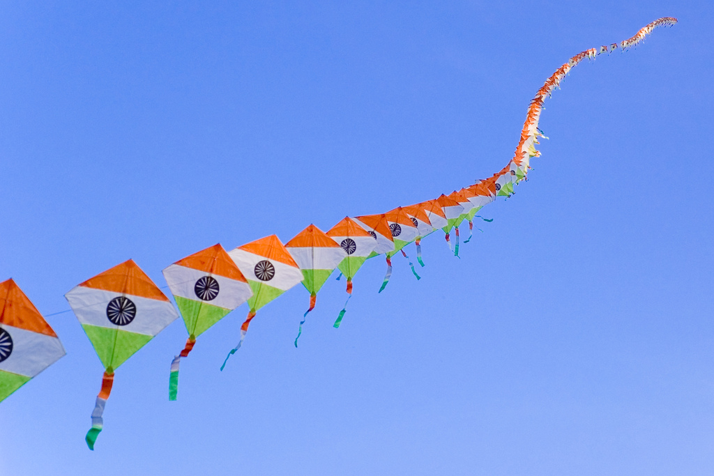 Many kites tied together in the colours of the Indian national flag.