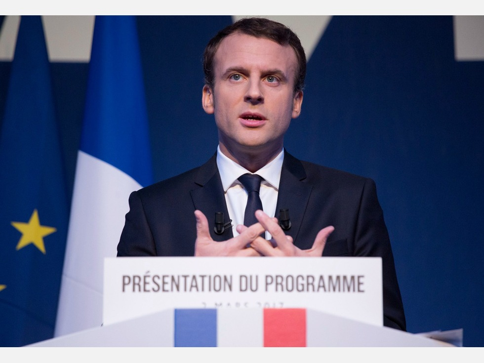 French president Emmanuel Macron (since May 2017) standing at a lectern which says