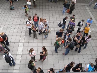 Blick von oben auf junge Leute, die auf einem gepflasterten Platz in Grüppchen zusammenstehen
