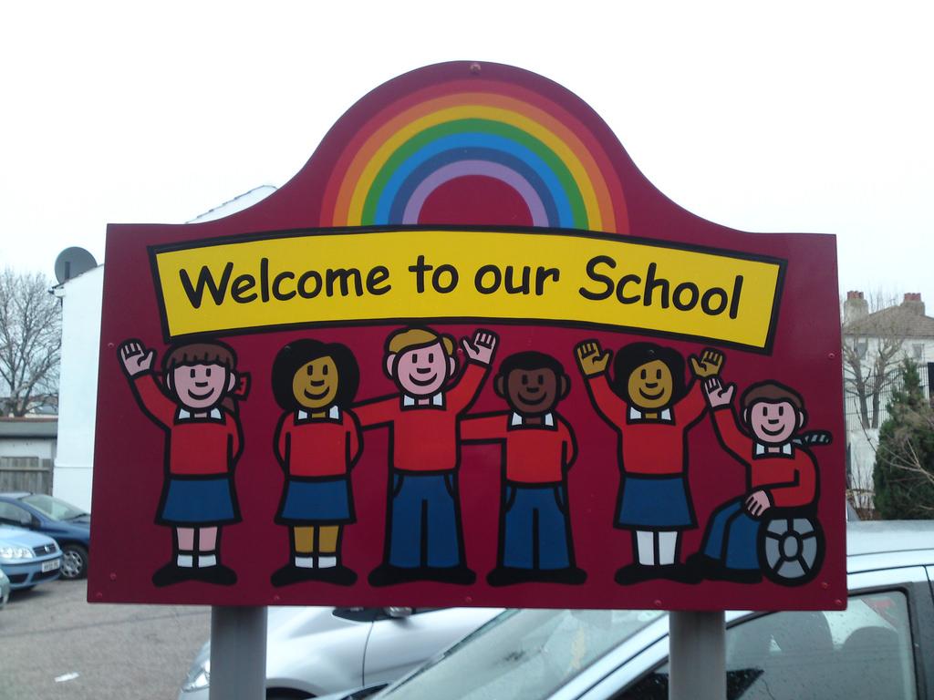 Ein gezeichnetes Schild vor einer Schule. Darauf zu sehen sind Kindern mit verschiedenem Migrationshintergrund, ein Kind mit einem Rollstuhl sowie ein regenbogen hinter den Kindern.