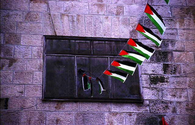 Small Palestinian flags in front of a window in Gaza city.