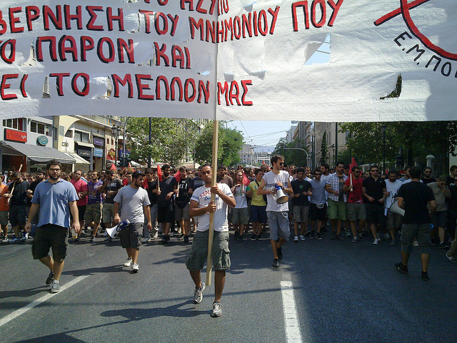 A crowd with the persons in the front row holding up a banner with a Greek inscript.