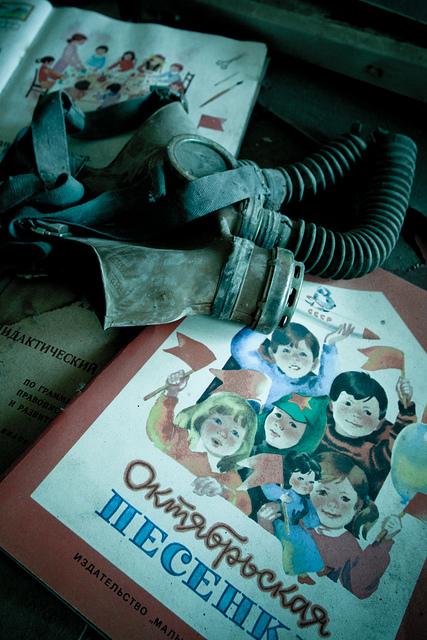 Ein ukrainisches Schulbuch und eine Gasmaske liegen in einer verlassenen Schule in einer Stadt nahe Tschernobyl, Ukraine.