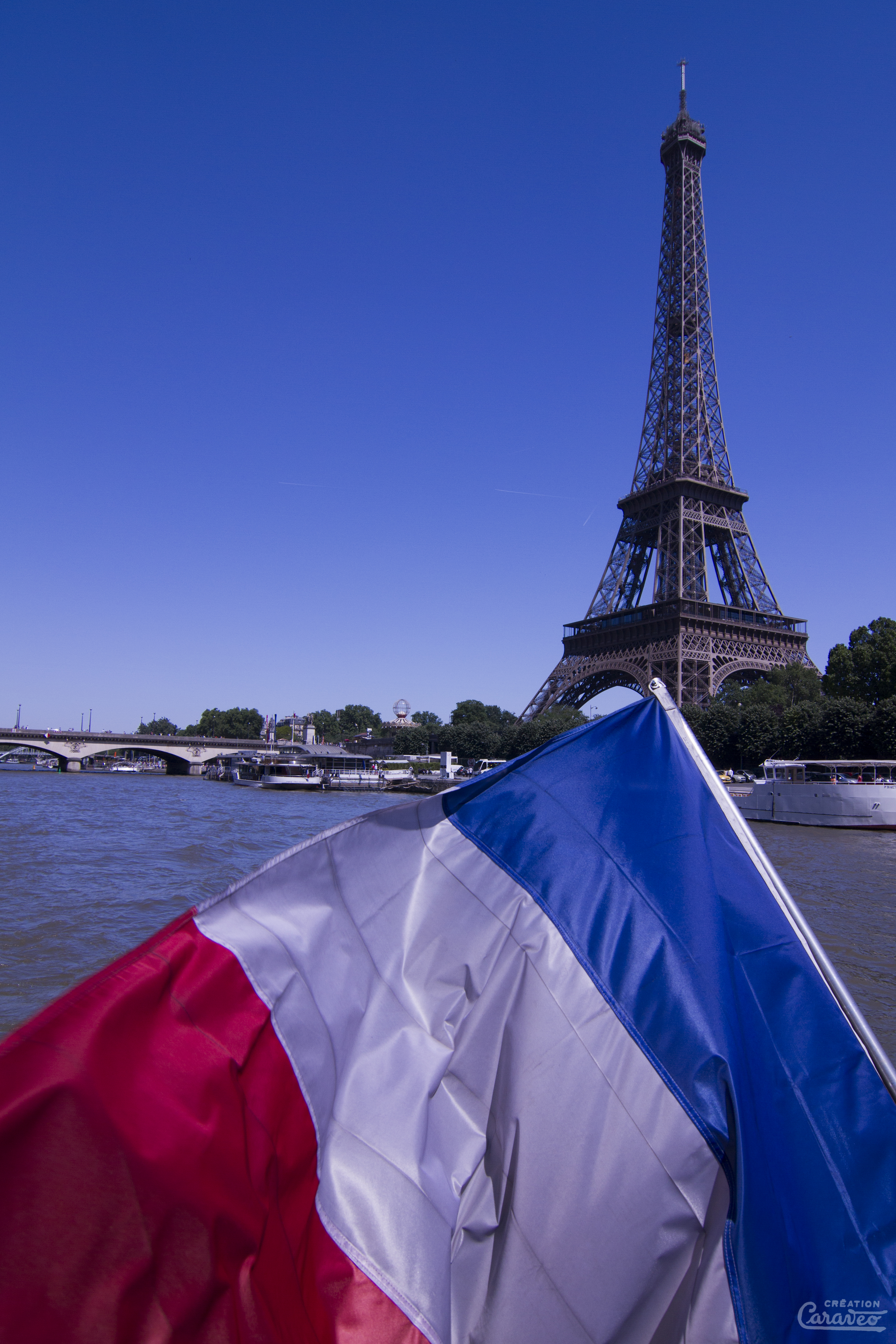 The French flag with the national colours blue, white, and red in front of the Eiffel Tower in Paris.