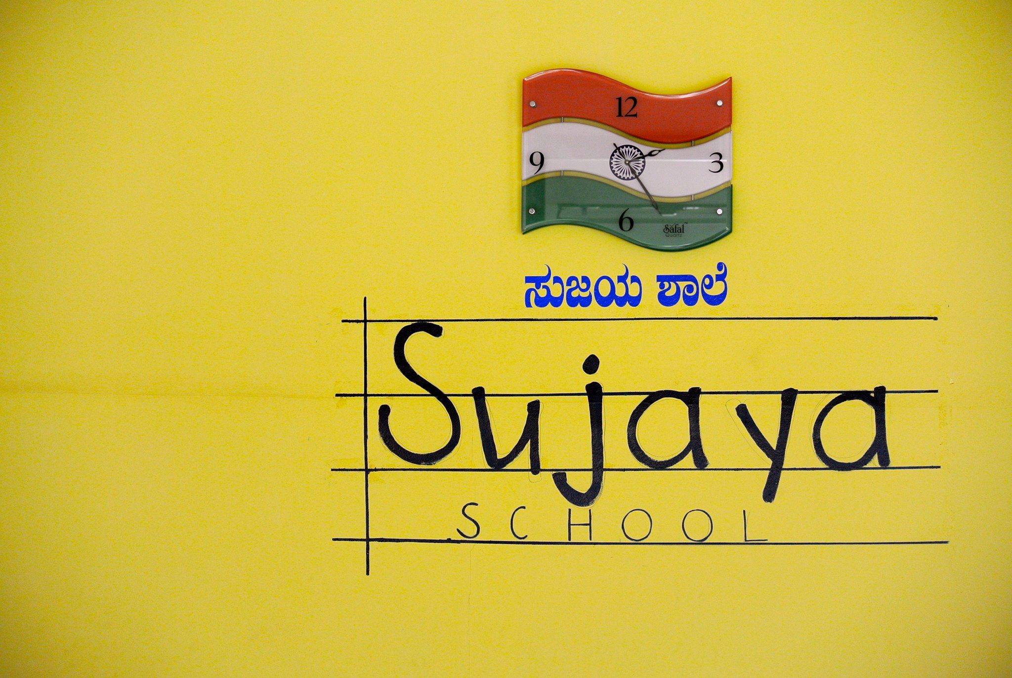 Sujaya school hand written in latin on a ledger line, above there is indian script ('kannada') and the national flag of India.