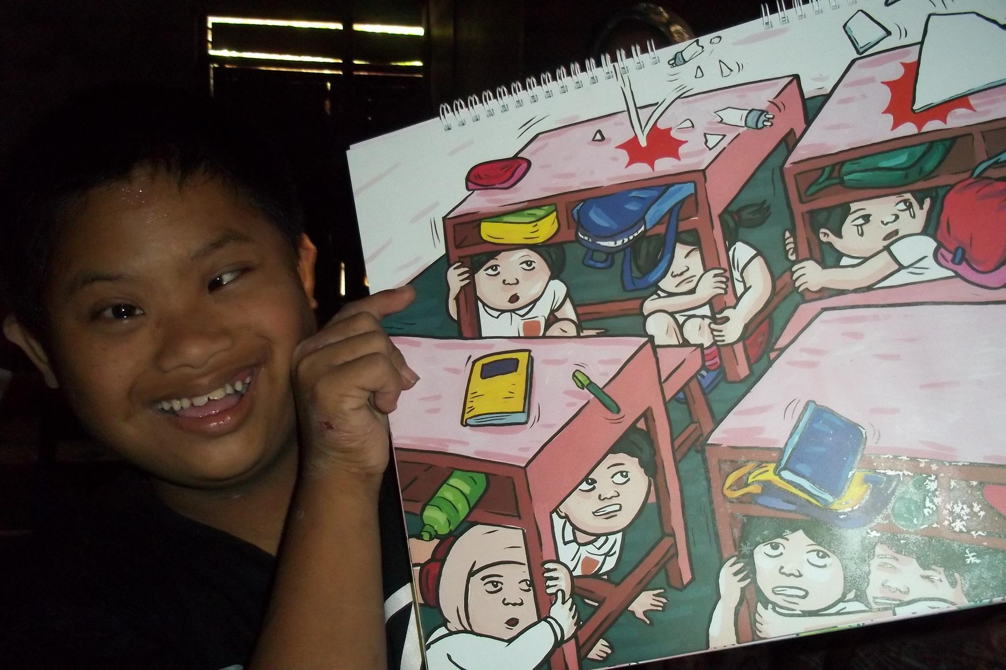 Ein Kind mit Down-Syndrom hält ein gezeichnetes Bild in der Hand von einer Schulklasse, bei der sich die Kinder vor herunterfallenden Dingen (Erdbeben?) unter Tischen in Schutz bringen.