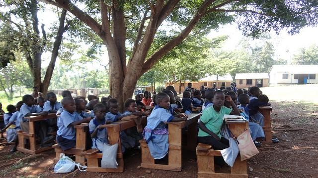 Schulkinder in Kenia sitzen auf Schulbänken im Freien unter Bäumen.