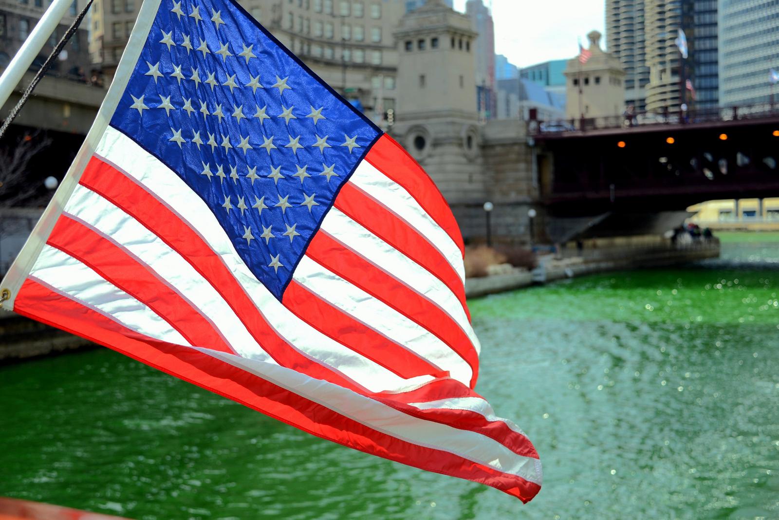 Nationalflagge der USA vor einem Fluss in Chicago
