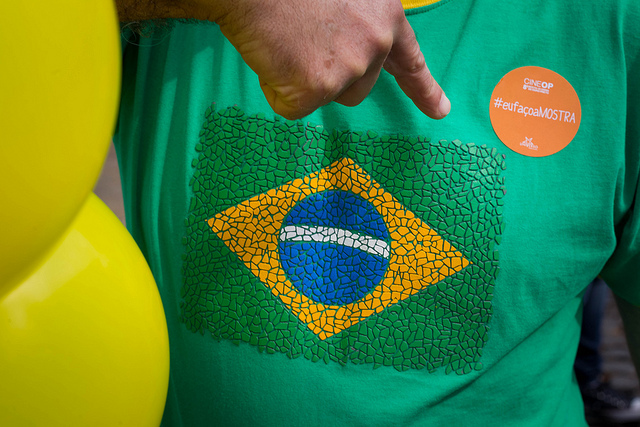 A hand's index finger is pointing towards a green t-shirt with the Brasilian national flag on it.