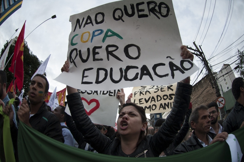 A protesting crowd, in the centre of the picture a young woman holding a poster where you can read 'I don`t want the Cup, I want education' (in Portuguese)
