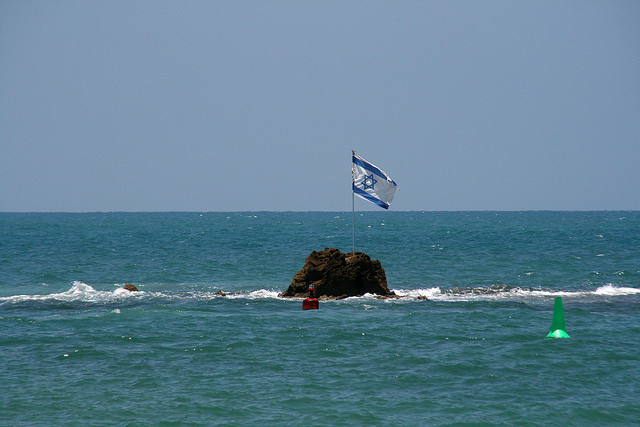 Israel Flag on a rock in the sea in front of Tel-Aviv-Jaffa.