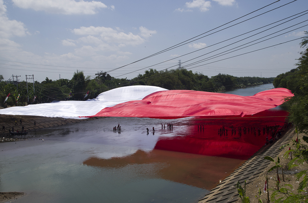 Eine riesige indonesische Nationalflagge ist wie ein Sonnendach über einen Fluss gespannt.