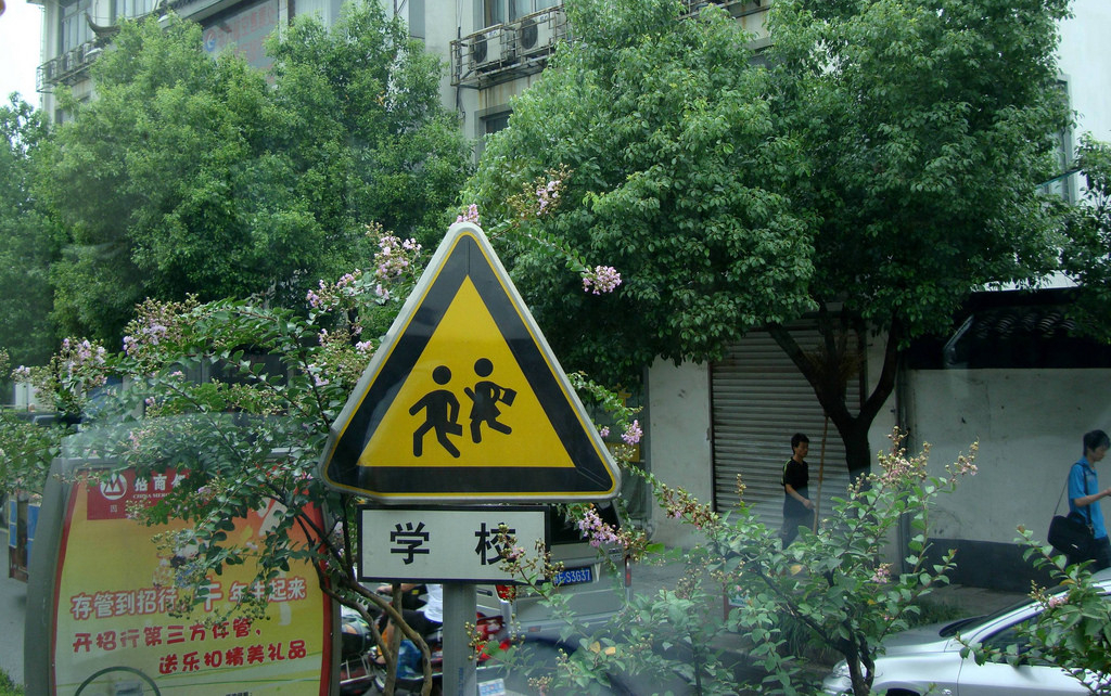 Street Sign with stylised school children and a Chinese inscription in Suzhou, China