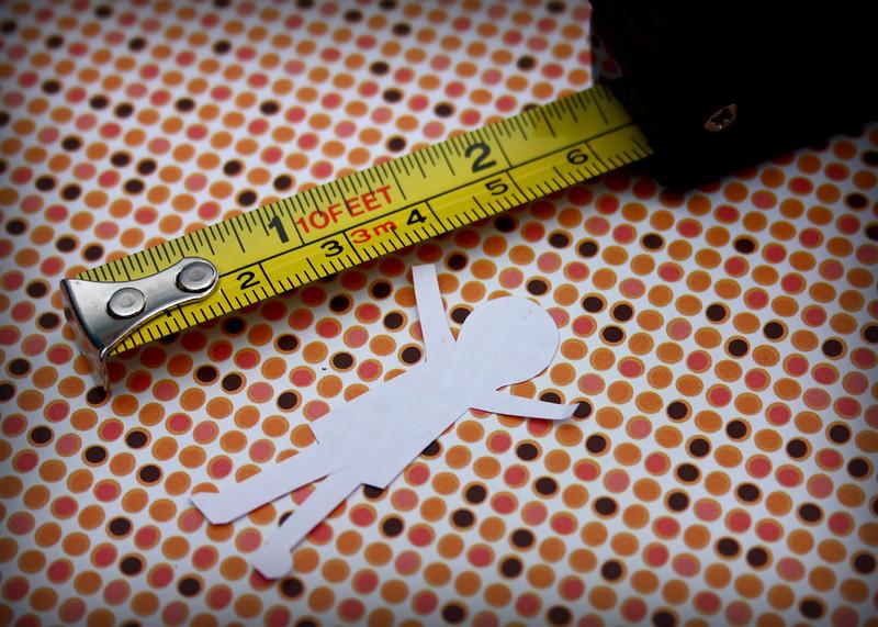 Ein Papiermännchen wird mit einem Maßband vermessen.