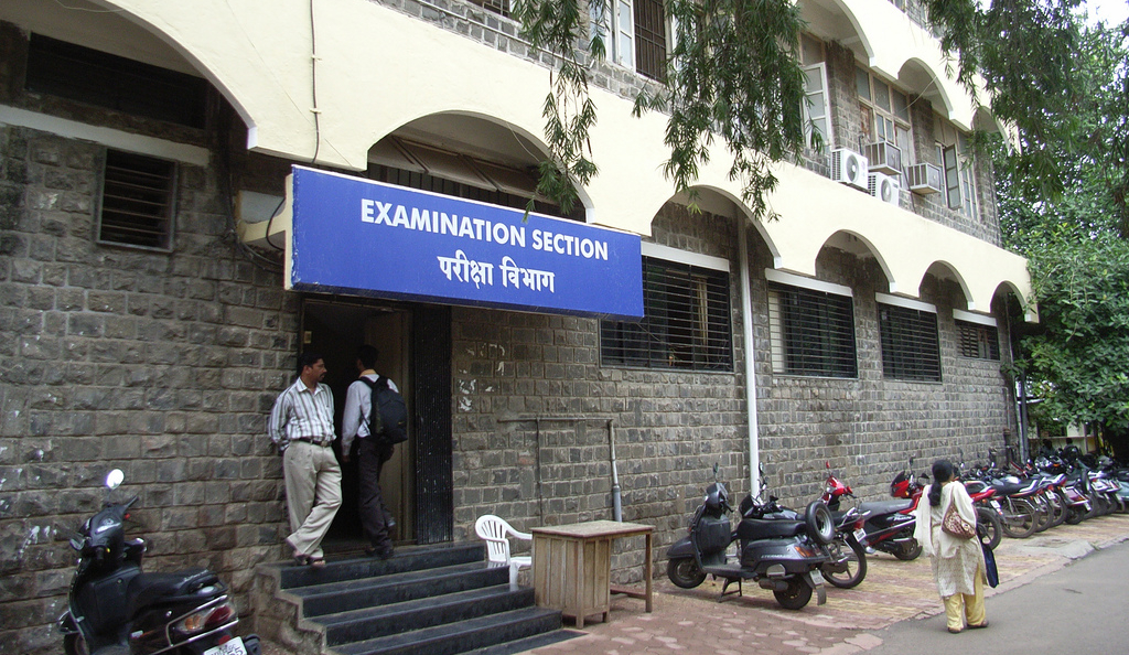 A sign above an entrance where you can read in Latin and Indian script (in English and Marathi?): Examination section.