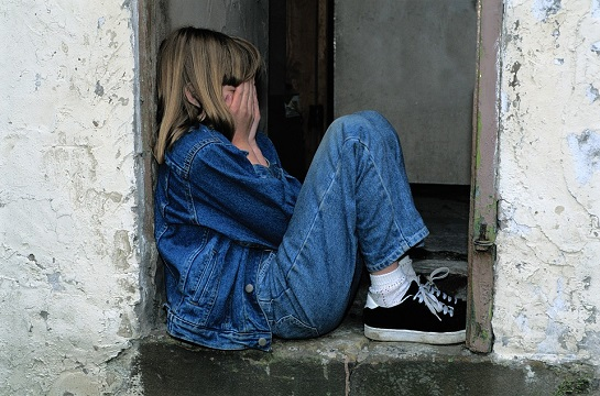 Verzweifeltes Kind hockt allein in einem Hauseingang