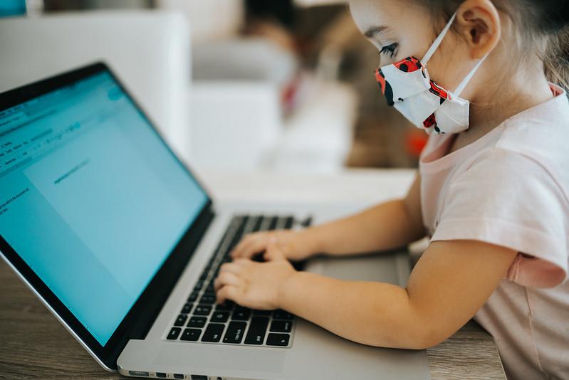 Ein kleines Mädchen sitzt mit Atemschutzmaske an einem Laptop.