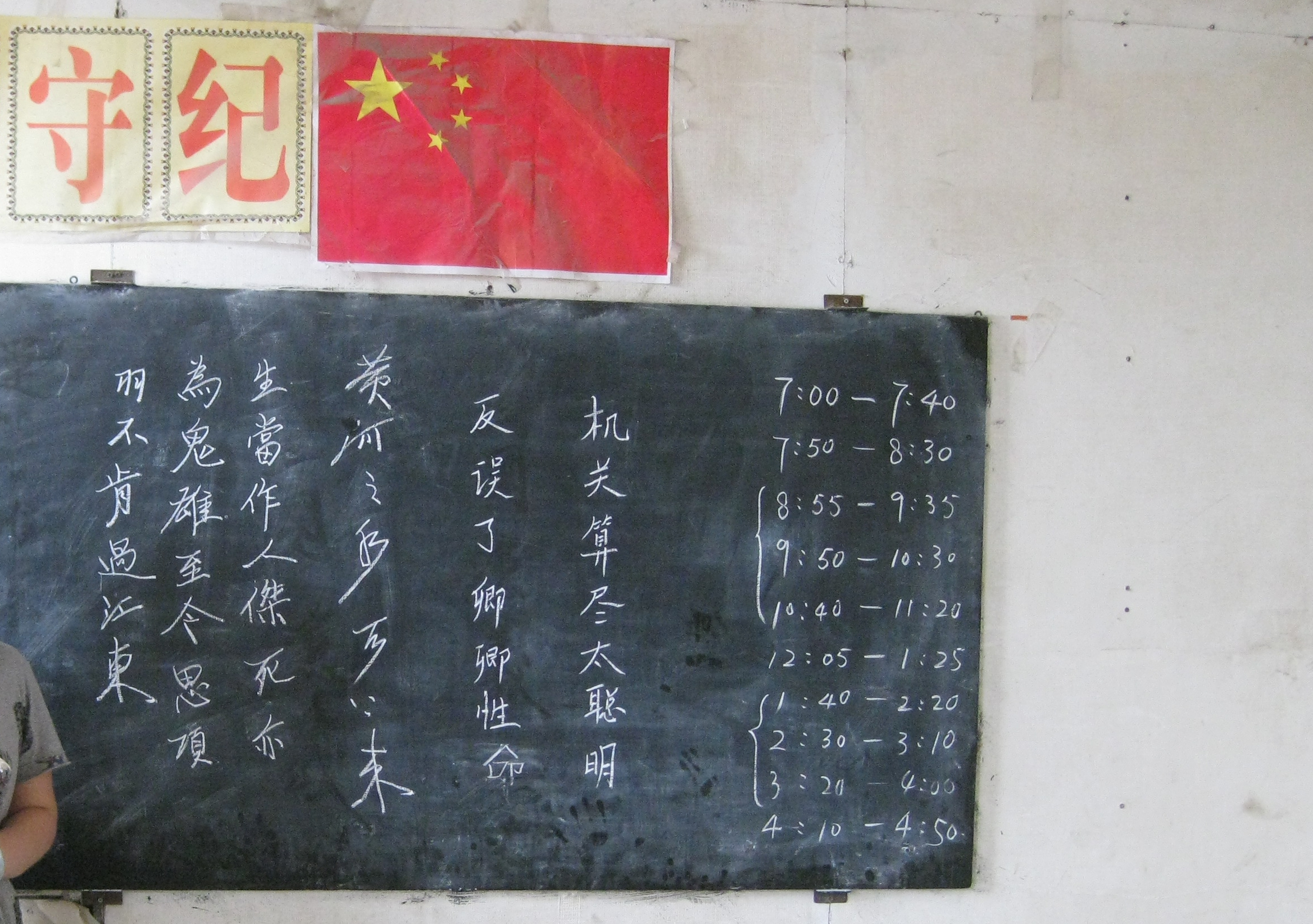 A blackboard with Chinese script in a school. Above the board hangs the national flag of China.