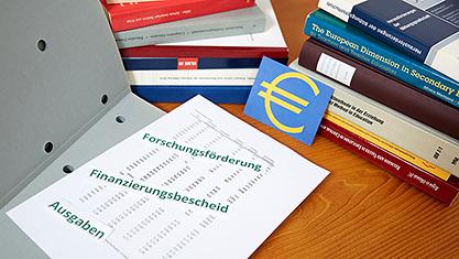 Aktenordner mit Forschungsförderung, Finanzierungsbescheid, Ausgaben, EURO-Symbol und Büchern