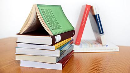 Bücherstapel mit Buch als Spitzdach
