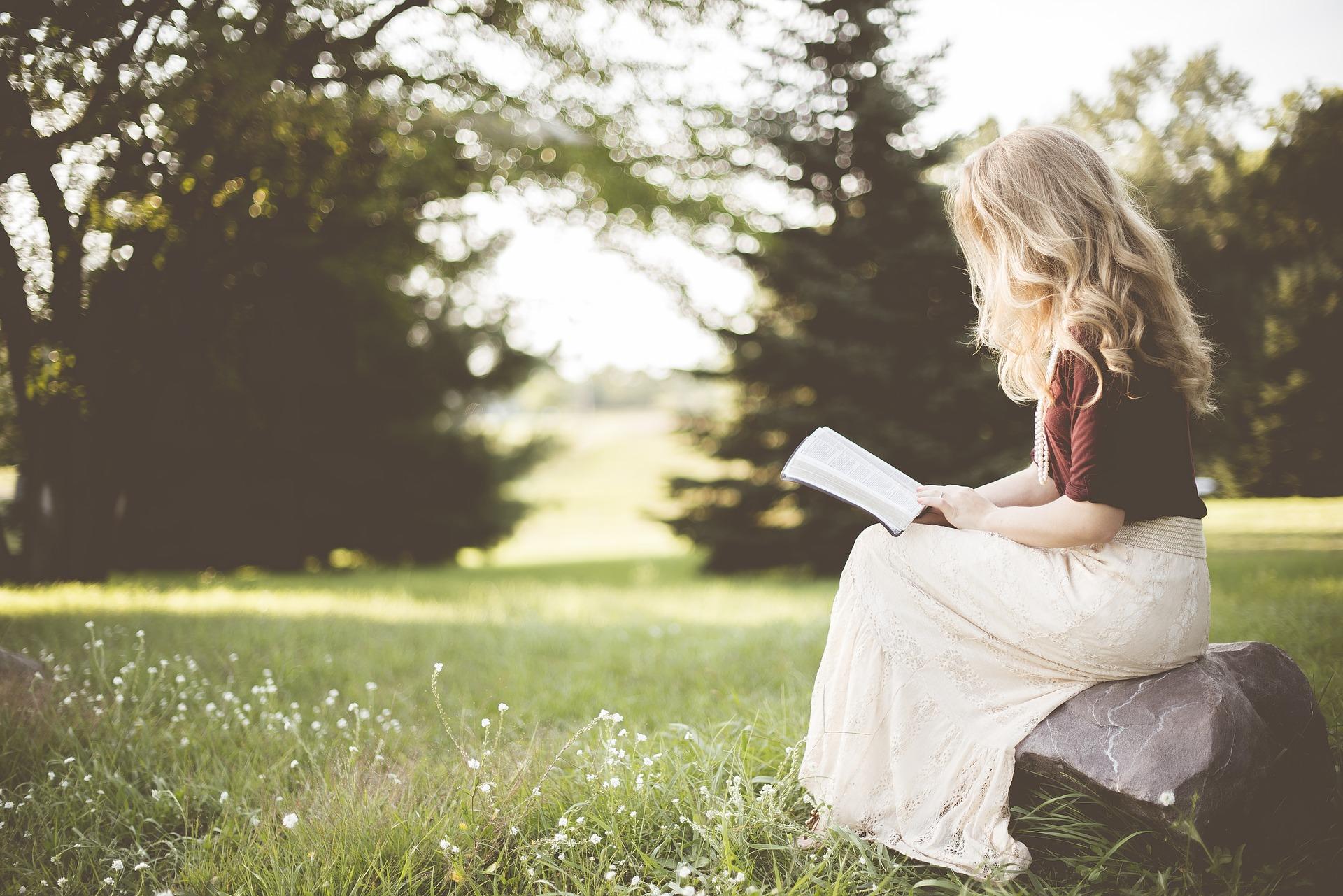 Ein Mädchen sitzt in der Natur und liest ein Buch.