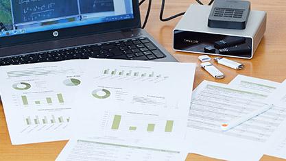 Laptop-Computer mit Statistikausdrucken, mobiler Festplatte und USB-Sticks