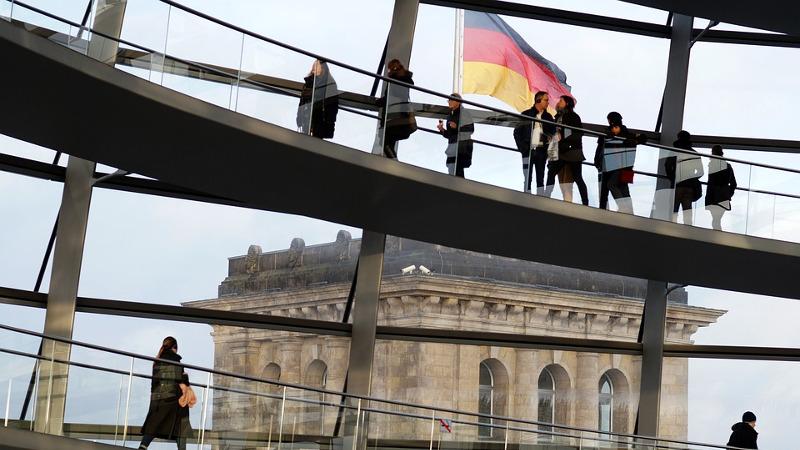Innenansicht der Kuppel des Reichstagsgebäudes mit Besuchern und deutscher Flagge im Hintergrund